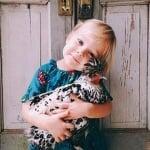 Малко момиченце прегръща кокошка