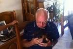 Възрастен човек получава кученце за подарък